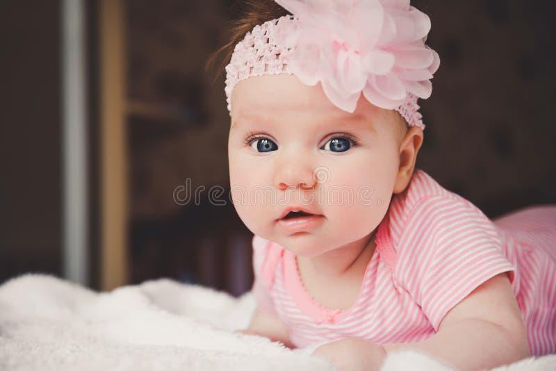 逗人喜爱的3个月在家躺下在一张白色床上的桃红色的微笑的女婴看照相机 大开放眼睛 婴儿 图库摄影