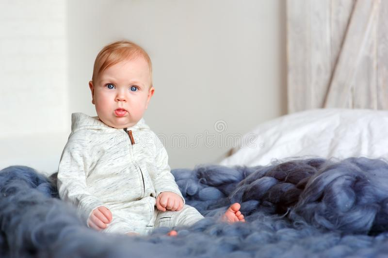 逗人喜爱的8个月大女婴画象坐在特大被编织的毯子的床 免版税图库摄影