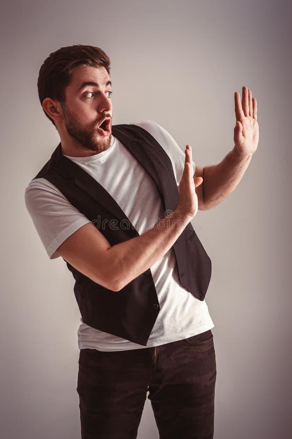 逗人喜爱的年轻人吓唬了有胡子的人在衬衣和背心在灰色背景 免版税库存照片