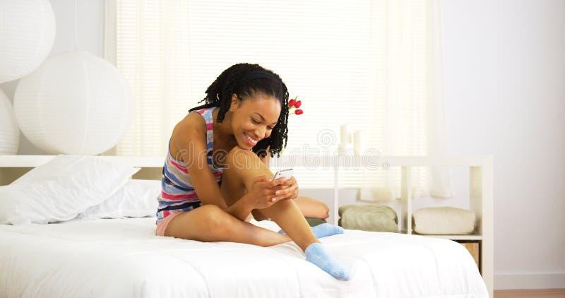逗人喜爱的黑人妇女坐床发短信 库存图片