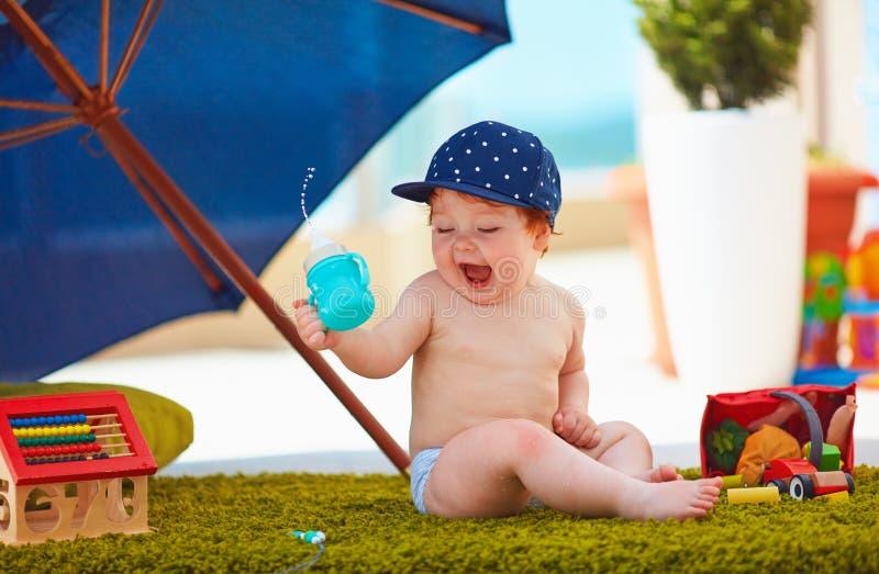 逗人喜爱的婴儿男婴获得乐趣户外温暖的夏日 库存照片