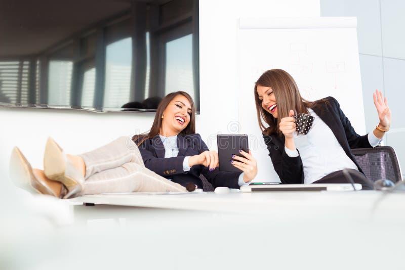 逗人喜爱的年轻女工在办公室休息 库存照片