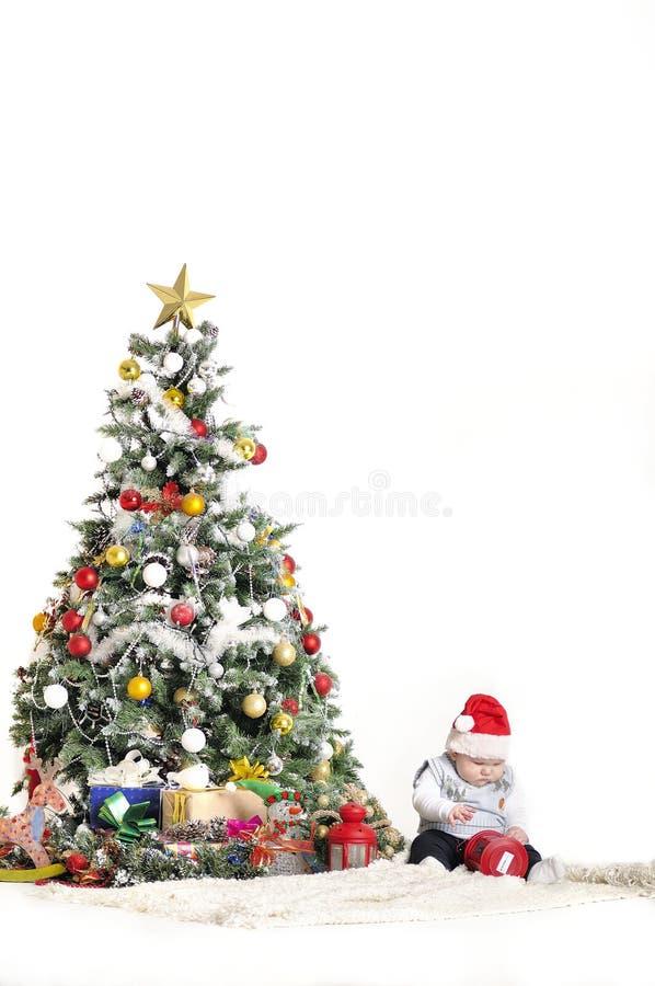 逗人喜爱的婴孩使用与圣诞树装饰的一个年男孩 图库摄影