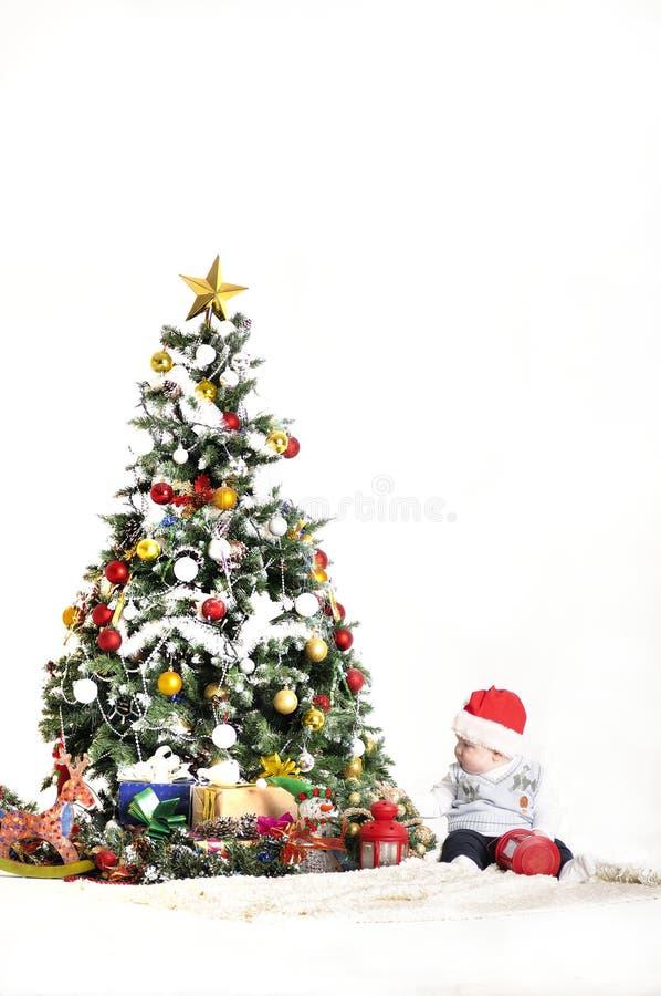 逗人喜爱的婴孩使用与圣诞树装饰的一个年男孩 库存照片