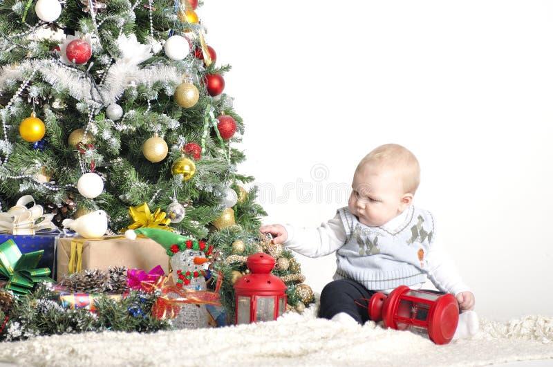 逗人喜爱的婴孩使用与圣诞树装饰的一个年男孩 库存图片