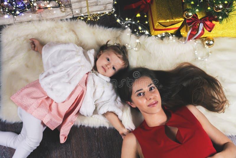 逗人喜爱的婴孩和妈咪在圣诞树附近 新年2017年 库存图片
