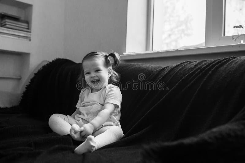 逗人喜爱的婴孩在一把黑椅子在家坐 免版税库存照片