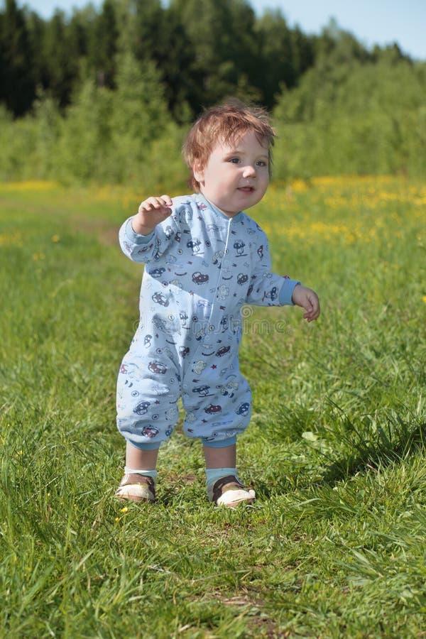 逗人喜爱的婴孩在绿草站立在森林附近 库存照片