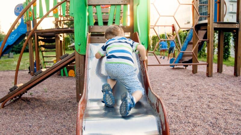 逗人喜爱的3岁照片上升和乘坐在儿童操场的大幻灯片的小孩男孩在公园 免版税库存图片