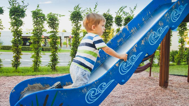 逗人喜爱的3岁照片上升和乘坐在儿童操场的大幻灯片的小孩男孩在公园 免版税库存照片