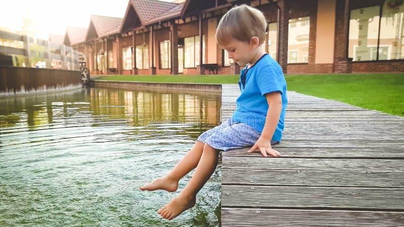 逗人喜爱的3岁照片坐riverebank在水运河在老镇和飞溅水的小男孩与脚 免版税图库摄影
