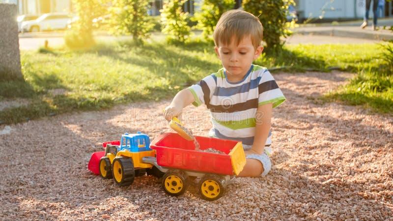 逗人喜爱的3岁画象坐操场在公园和使用与五颜六色的塑料玩具卡车的小孩男孩 库存照片