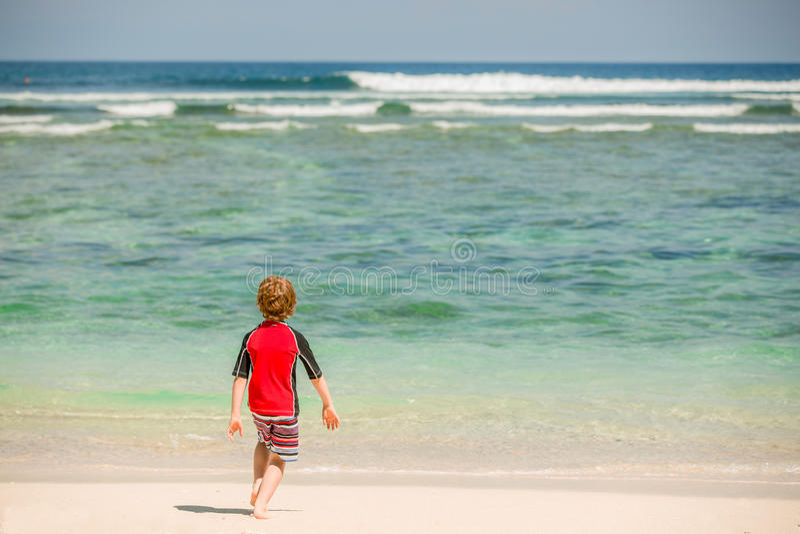 逗人喜爱的7岁红色rushwest游泳衣的男孩在与白色沙子和绿色海洋的热带海滩 库存照片