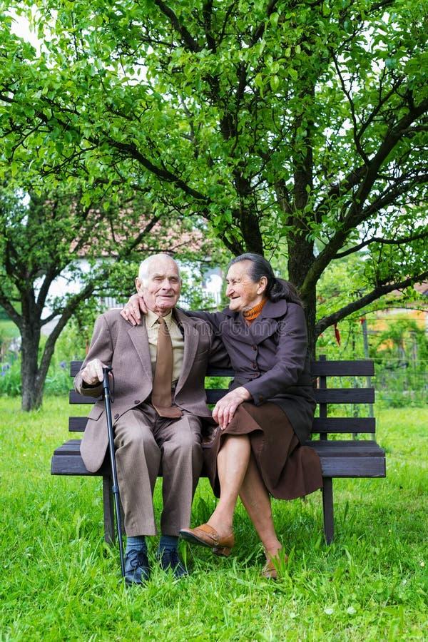 逗人喜爱的80正岁在他们的庭院里与摆在为一张画象的夫妇结婚 永远爱概念 库存照片