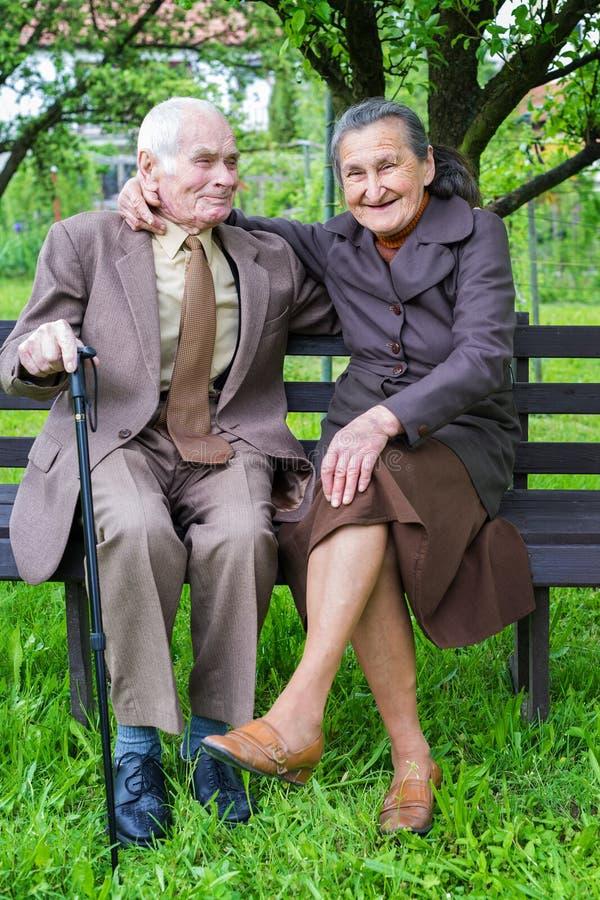 逗人喜爱的80正岁在他们的庭院里与摆在为一张画象的夫妇结婚 永远爱概念 免版税库存图片