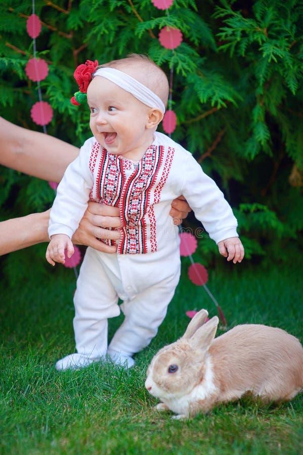逗人喜爱的滑稽的愉快的婴孩用做他的第一步的兔子在绿草 免版税库存照片