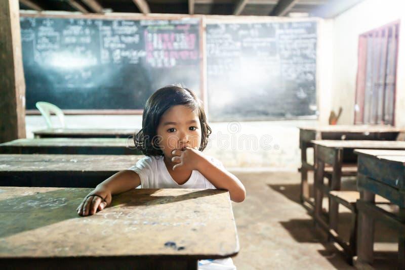 逗人喜爱看照相机的一个小高棉女孩在教室小学 o 库存照片