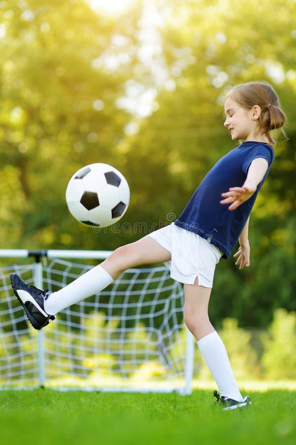 逗人喜爱获得矮小的位的足球运动员打一足球的乐趣在晴朗的夏日 孩子的体育活动 库存照片