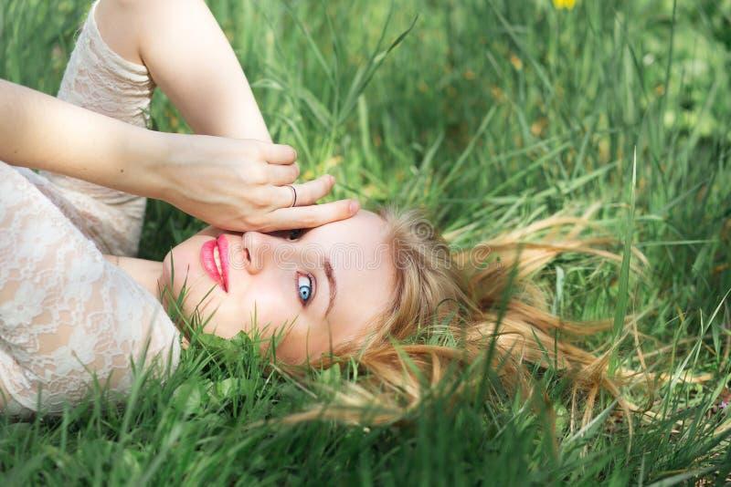 逗人喜爱蓝眼睛白肤金发说谎在春天草 有红色嘴唇的愉快少妇和自然在白色有花边的礼服组成 库存照片