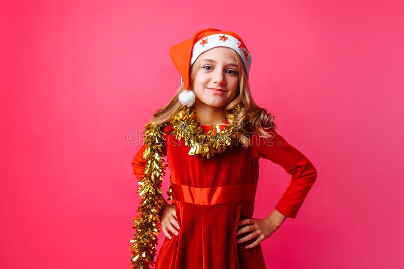 逗人喜爱青少年在圣诞老人帽子和与在微笑在红色ba的脖子的闪亮金属片 免版税图库摄影