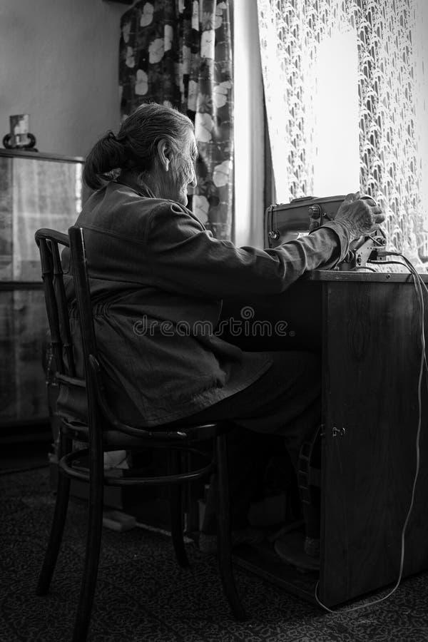 逗人喜爱80使用葡萄酒缝纫机的正岁资深妇女 可爱的年长妇女缝合的衣裳的黑白图象 免版税库存照片