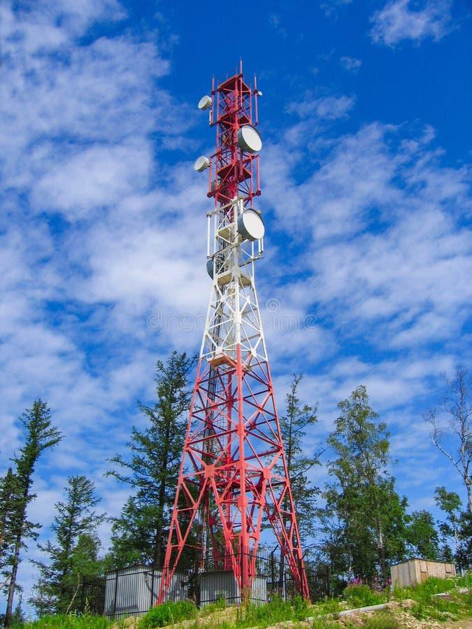 通信塔反对天空和绿色树的 图库摄影