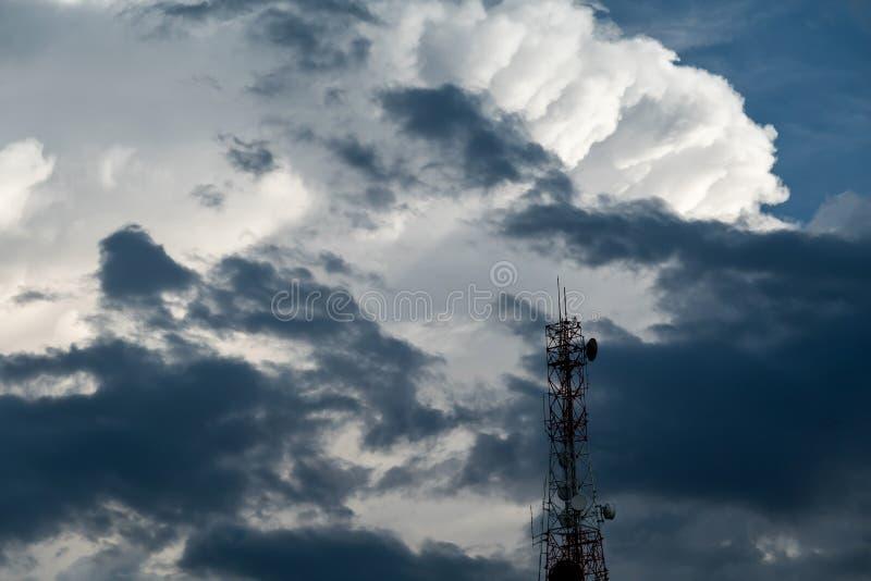 通信天线塔和中继器与白色蓬松云彩的在天空蔚蓝背景中 免版税图库摄影
