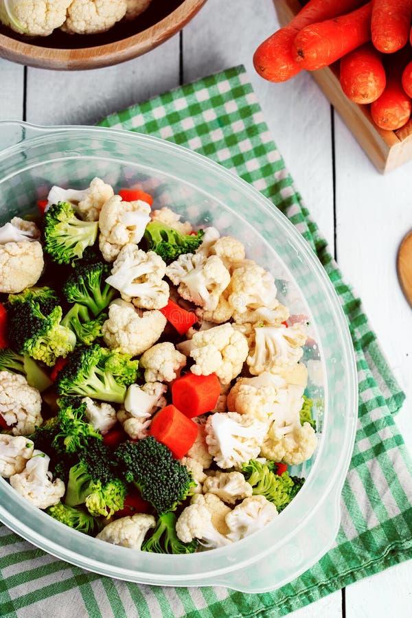 通入蒸汽的新鲜蔬菜在厨房里,准备一顿健康膳食用硬花甘蓝,花椰菜和红萝卜 库存照片