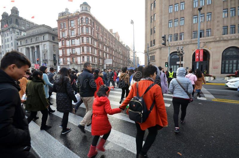 通勤者在障壁的一条繁忙的行人穿越道在上海,中国 库存图片
