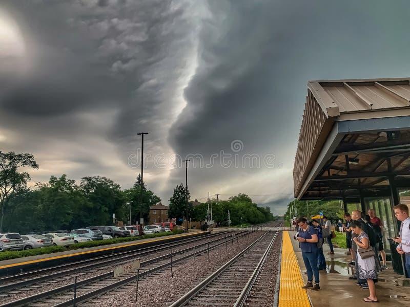 通勤者等待火车,当站立在芝加哥郊区驻地平台早晨风雨如磐的夏天时 库存照片