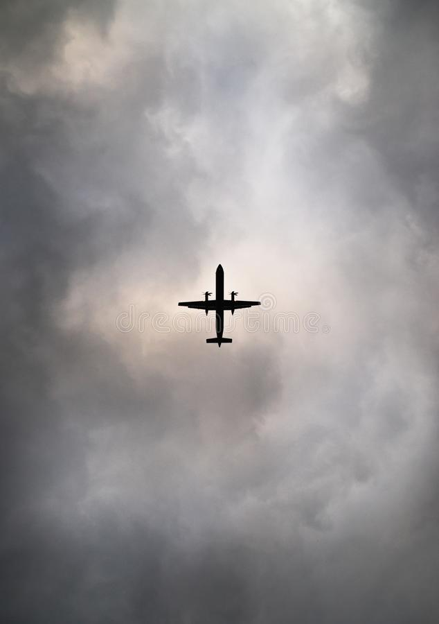 通勤者飞机现出轮廓反对多云天空 库存图片
