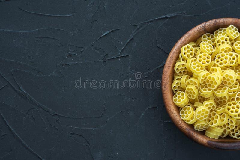 通心面在一个木碗的ruote面团在从边的黑织地不很细背景 与上面的特写镜头 空位 免版税库存照片