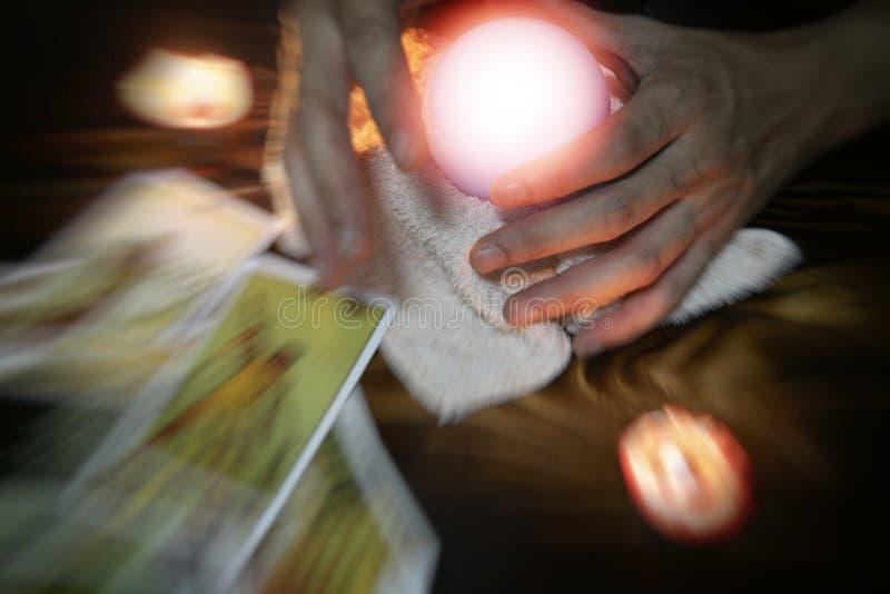 通灵读书和洞察力概念-水晶球算命先生一定手和读占卜,与作用的占卜用的纸牌 库存照片