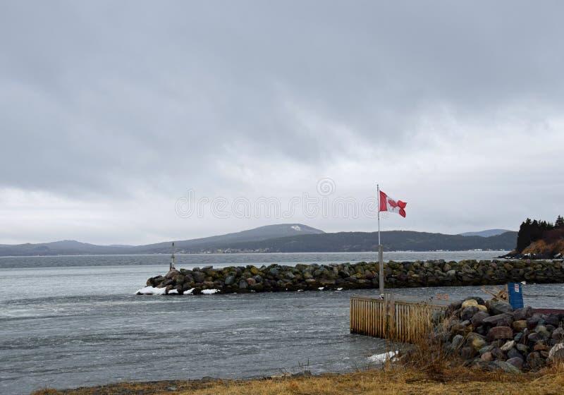 通过一个旗杆的看法有往海湾的加拿大旗子的 库存图片