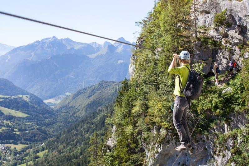 通过上升的ferrata,鞔具横穿索桥的妇女在山 库存照片