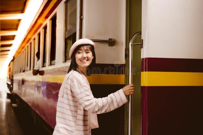 通过使用公开火车,俏丽的妇女进入火车在去的后面家的火车站 可爱的美女得到 免版税图库摄影