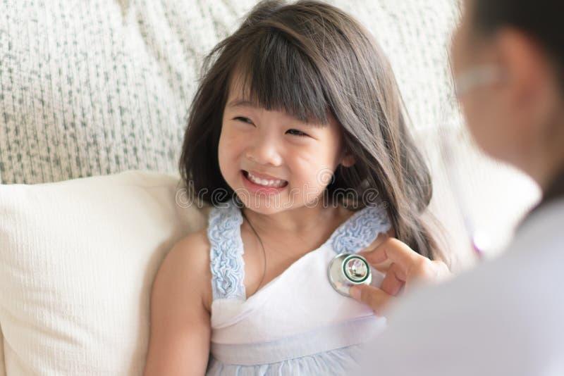 通过使用听诊器,篡改审查一个亚裔逗人喜爱的小女孩 免版税库存图片