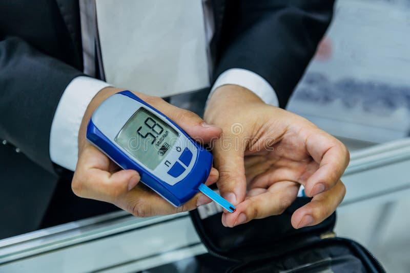 通过使用数字式glucometer,供以人员在血液的测量的葡萄糖水平 免版税库存照片