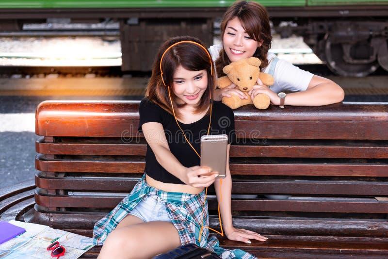 通过使用智能手机a,一起美好的妇女或朋友selfies 库存图片