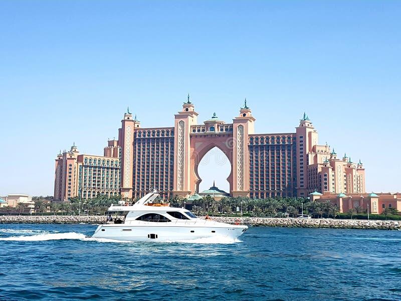 通过在亚特兰提斯前面著名5个星旅馆的一条美丽的游艇的图片朱美拉棕榈岛位于迪拜 免版税图库摄影