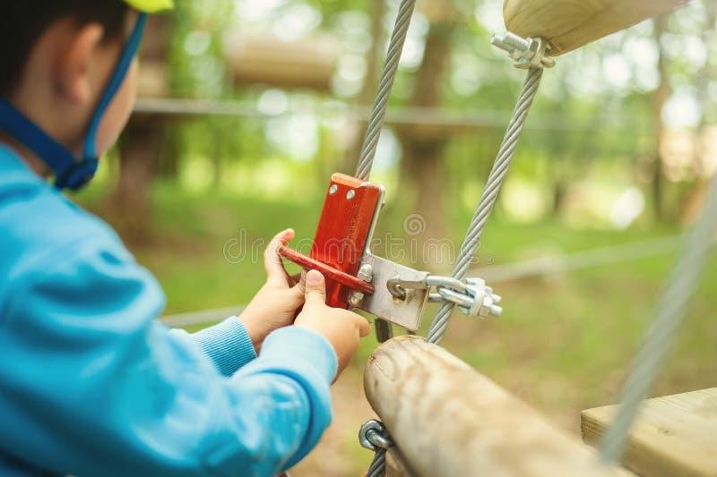 通过在树中的年轻男孩电缆路径,极限运动在冒险公园 库存图片