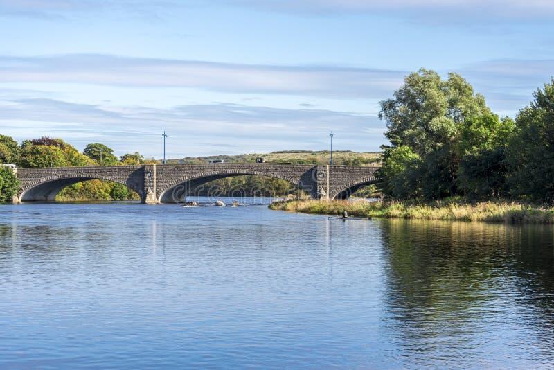 通过在桥梁下的两三艘皮船,当实践荡桨在河迪伊,阿伯丁时 库存照片