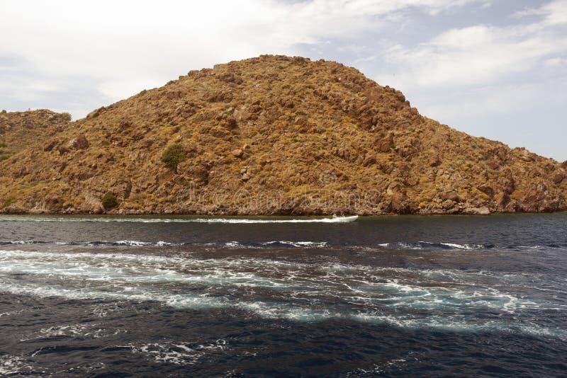 通过在爱琴海的一个岩质岛和汽艇的看法在希腊 免版税库存照片