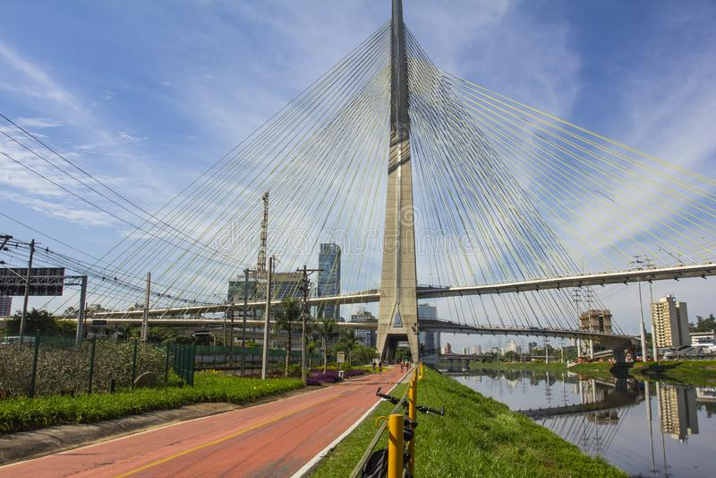 通过在缆绳被停留的桥梁下的美丽的自行车道路在Pinheiros河旁边在圣保罗,巴西 免版税库存图片