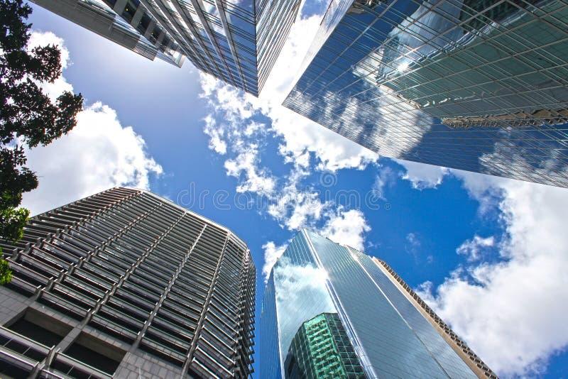 通过摩天大楼反射云彩的和在CBD布里斯班昆士兰澳大利亚的其他大厦观看看蓝色多云天空 免版税库存照片