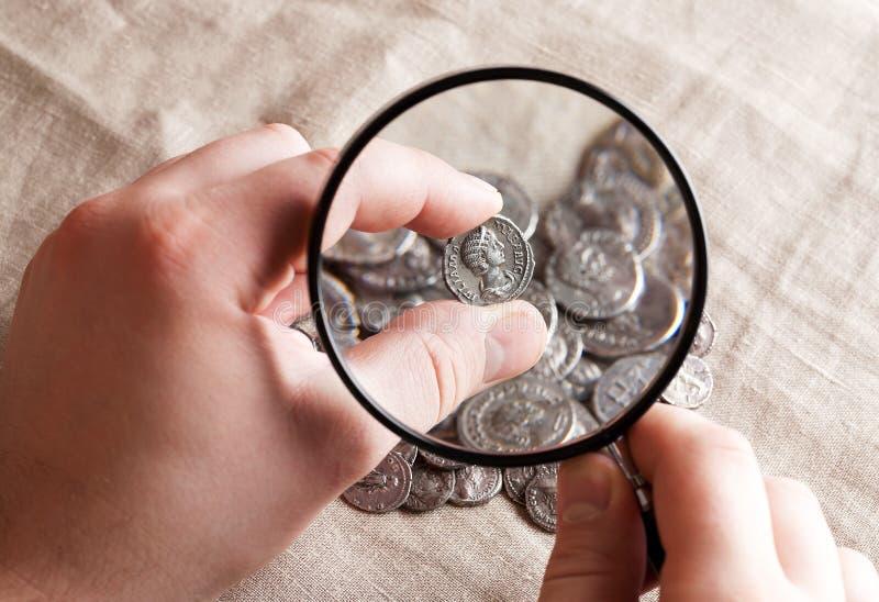通过放大镜被看见的堆古色古香的硬币 免版税图库摄影