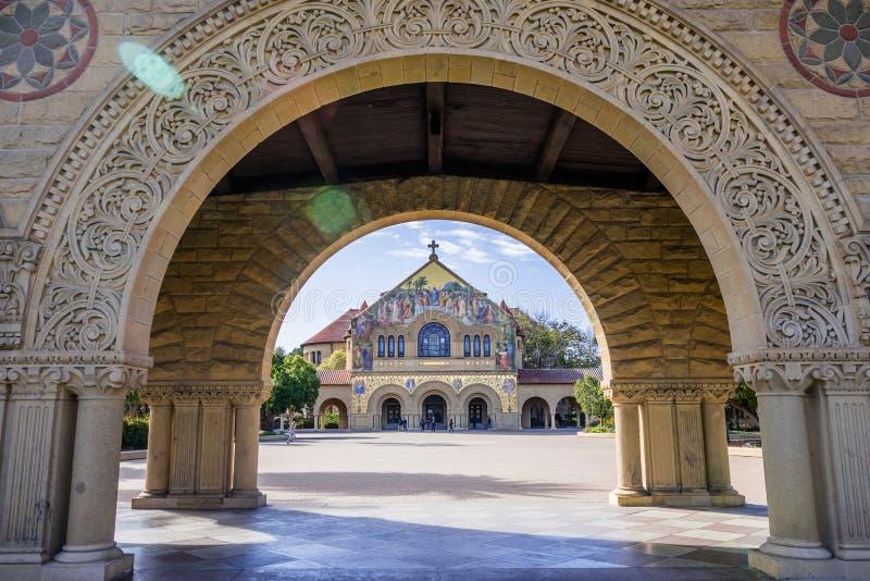 通过曲拱被看见的斯坦福的纪念教会在围拢主要方形字体的柱廊 库存照片