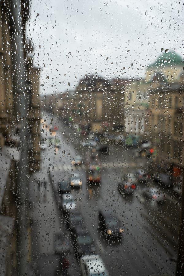 通过汽车挡风玻璃被观看的Defocussed交通盖在雨中 免版税库存照片