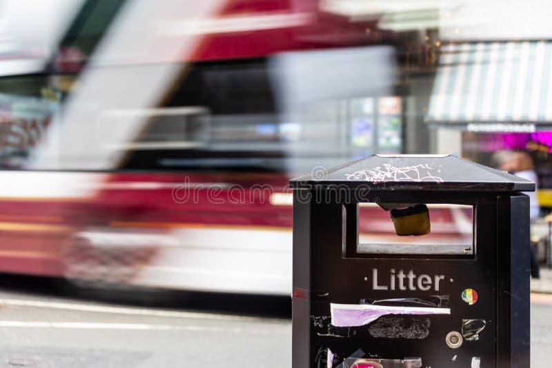 通过沿在迷离的街道的红色和白色公共汽车与在前景的一个垃圾桶 免版税库存照片
