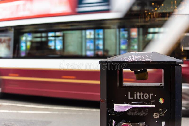 通过沿在迷离的街道的红色和白色公共汽车与在前景的一个垃圾桶 库存照片